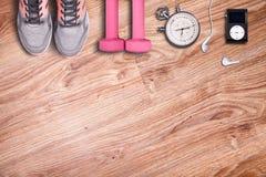 Gimnasio de la aptitud y equipo corriente Pesas de gimnasia y zapatillas deportivas, cronómetro análogo y jugador de música Foto de archivo