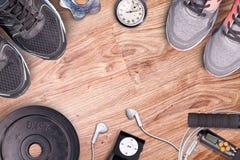 Gimnasio de la aptitud y equipo corriente Pesas de gimnasia y zapatillas deportivas, cronómetro análogo y jugador de música Fotografía de archivo