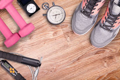 Gimnasio de la aptitud y equipo corriente Pesas de gimnasia y zapatillas deportivas, cronómetro análogo y jugador de música Imagen de archivo libre de regalías