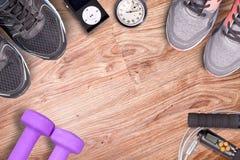 Gimnasio de la aptitud y equipo corriente Pesas de gimnasia y zapatillas deportivas, cronómetro análogo y jugador de música Hora  Fotografía de archivo libre de regalías