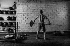 Gimnasio del entrenamiento de la vista posterior del hombre del levantamiento de pesas del Barbell Imagen de archivo