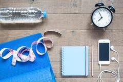 Gimnasio y concepto de la aptitud con el cuaderno, el smartphone y el despertador en la madera Fotos de archivo