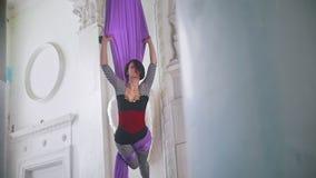 Gimnasta atractivo de la mujer joven que realiza la demostración acrobática del aire metrajes