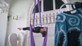 Gimnasta atractivo de la mujer joven que se realiza en la seda aérea - demostración acrobática emocionante, a cámara lenta metrajes