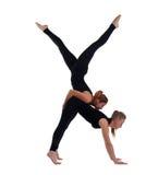 Gimnasta de dos mujeres en ejercicio acrobático de la demostración negra Imagen de archivo