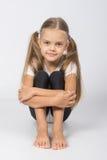 Gimnasta de la muchacha que se sienta en el piso que abraza sus piernas fotos de archivo