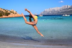 Gimnasta de la muchacha, salto, playa de Cerdeña, Oporto Istana que hace frente a la isla de Tavolara Imagenes de archivo