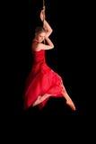 Gimnasta de la mujer en vestido rojo en cuerda en fondo negro Imagen de archivo
