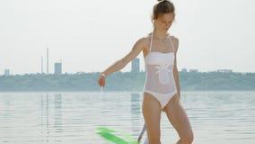 Gimnasta de la mujer joven en un cuerpo blanco en un baile de la playa arenosa con la cinta gimnástica Verano, amanecer almacen de metraje de vídeo