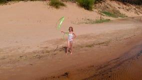 Gimnasta de la mujer joven en un cuerpo blanco en un baile de la playa arenosa con la cinta gimnástica Verano, amanecer almacen de video