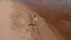 Gimnasta de la mujer joven en un cuerpo blanco en un baile de la playa arenosa con la cinta gimnástica Verano, amanecer metrajes