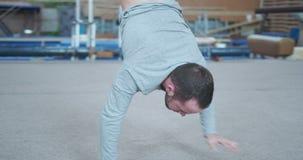Gimnasta de sexo masculino que camina en las manos en el gimnasio almacen de metraje de vídeo