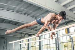 Gimnasta de sexo masculino que realiza posición del pino en barrases paralelas Foto de archivo libre de regalías