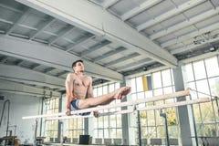 Gimnasta de sexo masculino que realiza posición del pino en barrases paralelas Imagen de archivo