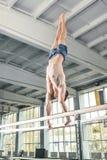 Gimnasta de sexo masculino que realiza posición del pino en barrases paralelas Fotos de archivo libres de regalías