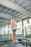Gimnasta de sexo masculino que realiza posición del pino en barrases paralelas Fotografía de archivo