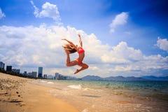 gimnasta delgado rubio en bikini en salto sobre la playa contra el cielo Foto de archivo