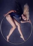 Gimnasta en un anillo en circo debajo de una bóveda Foto de archivo