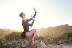 Gimnasta que adora con el sol detrás de ella Fotografía de archivo