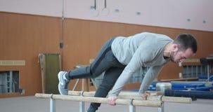 Gimnasta que ejercita en barrases paralelas en el gimnasio almacen de video