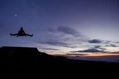 Gimnasta que hace el salto de las fracturas después de puesta del sol Foto de archivo