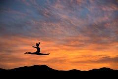Gimnasta que hace el salto de las fracturas en puesta del sol Foto de archivo libre de regalías