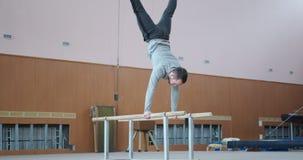 Gimnasta que hace posición del pino en barrases paralelas en el gimnasio almacen de video