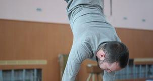 Gimnasta que realiza ejercicio del planche y de la posición del pino en el gimnasio almacen de video