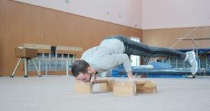 Gimnasta que realiza pectorales y posición del pino del planche en el gimnasio almacen de metraje de vídeo