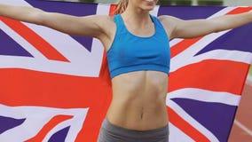 Gimnasta sonriente que celebra la victoria y sostener la bandera de Gran Bretaña, orgullo metrajes