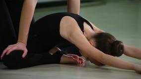 Gimnastas artísticos de las hermanas lindas delgadas del primer dos en ropa de deportes negra hacer calentamiento en gimnasio y r