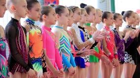 Gimnastas de las chicas jóvenes en gimnasio después del examen final en la escuela de Deriugina almacen de video