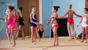 Gimnastas de las muchachas que tienen entrenamiento en gimnasio antes del examen en la escuela de Deriugina almacen de video