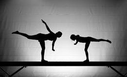 Gimnastas de sexo femenino en viga de balance Imagen de archivo libre de regalías