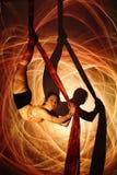 Gimnastyczka robi ćwiczeniu przeciw tłu ogniści paski Fotografia Royalty Free