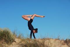 Gimnastyczka robi akrobatycznemu handstand na plaży Fotografia Royalty Free