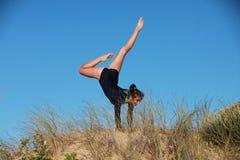 Gimnastyczka robi handstand na plaży Zdjęcie Stock