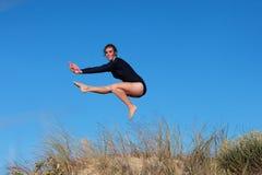 Gimnastyczka skacze joyfully na plaży Zdjęcia Royalty Free