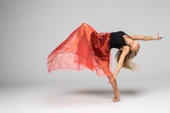 Gimnastyka tancerz w pracie tancerz z czerwonym jedwabiem w powietrzu na białym tle Zdjęcie Royalty Free