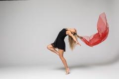 Gimnastyka tancerz w pracie tancerz z czerwonym jedwabiem w powietrzu na białym tle Fotografia Stock