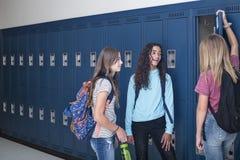 Gimnazjum ucznie opowiada i stoi ich szafką w szkolnym korytarzu zdjęcie royalty free