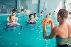 A ginástica aeróbica do Aqua, mulheres classifica com instrutor masculino imagem de stock