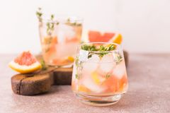 Gin bitter lemon with thyme and grapefruit. Fruit lemonade. Alcoholic cocktail gin bitter lemon with thyme and grapefruit. Fruit lemonade. Gray slate background Stock Photo
