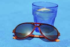 Gin cocktail with lemon in a blue glass and orange sunglasses Stock Image
