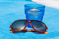 Gin cocktail with lemon in a blue glass and orange sunglasses Stock Photos