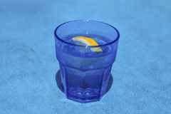 Gin cocktail with lemon in a blue glass Stock Images