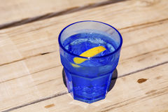 Gin cocktail with lemon slice on a wooden table. Gin cocktail with lemon slice in a blue glass  on a wooden background Stock Photos