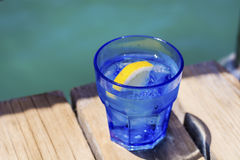 Gin cocktail with lemon slice on a wooden table Stock Images