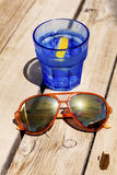 Gin cocktail with lemon slice on a wooden table with orange sunglasses Stock Images