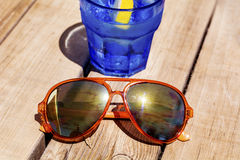 Gin cocktail with lemon slice on a wooden table with orange sunglasses Royalty Free Stock Image
